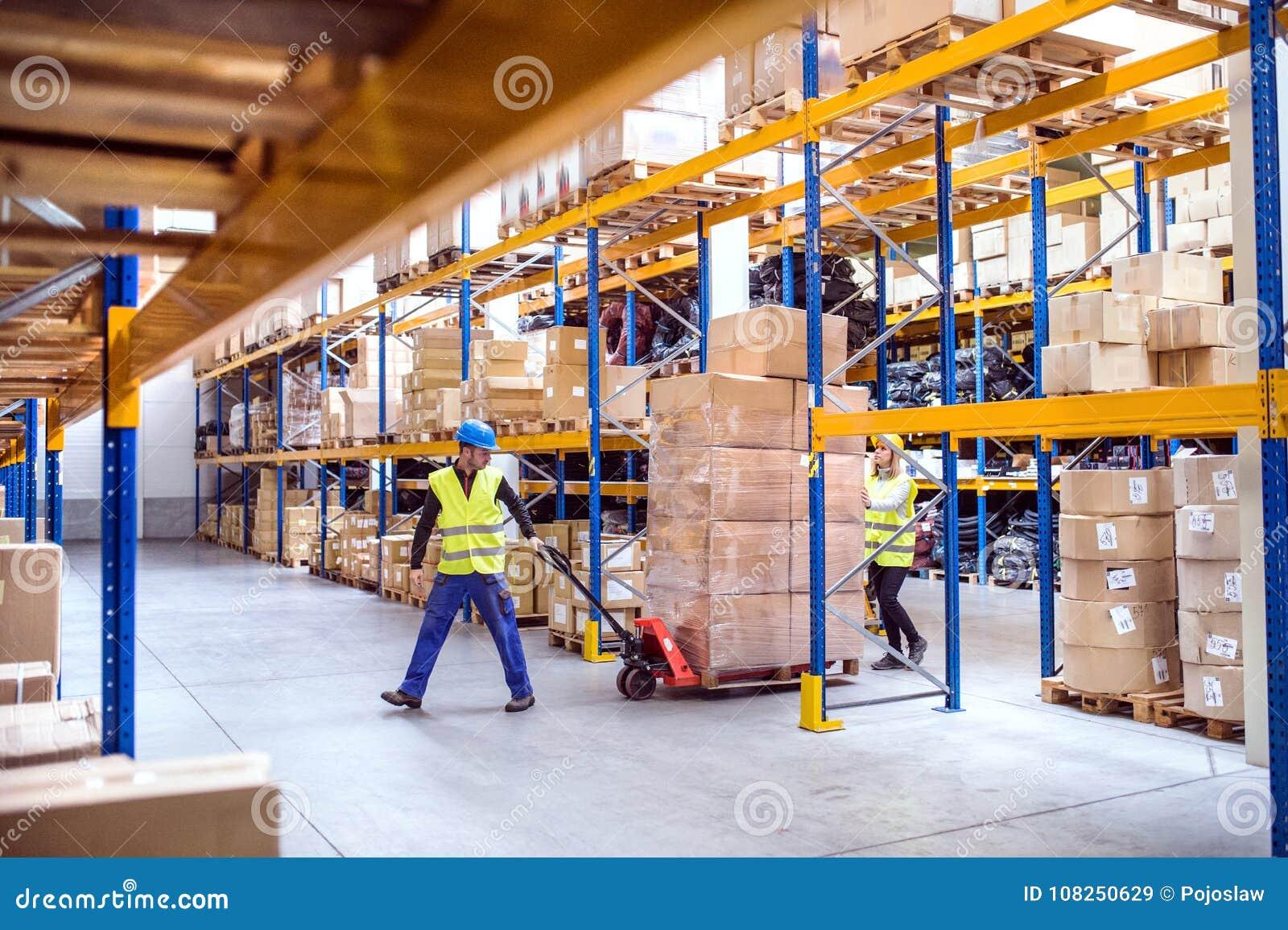 Работники склада вытягивая тележку паллета
