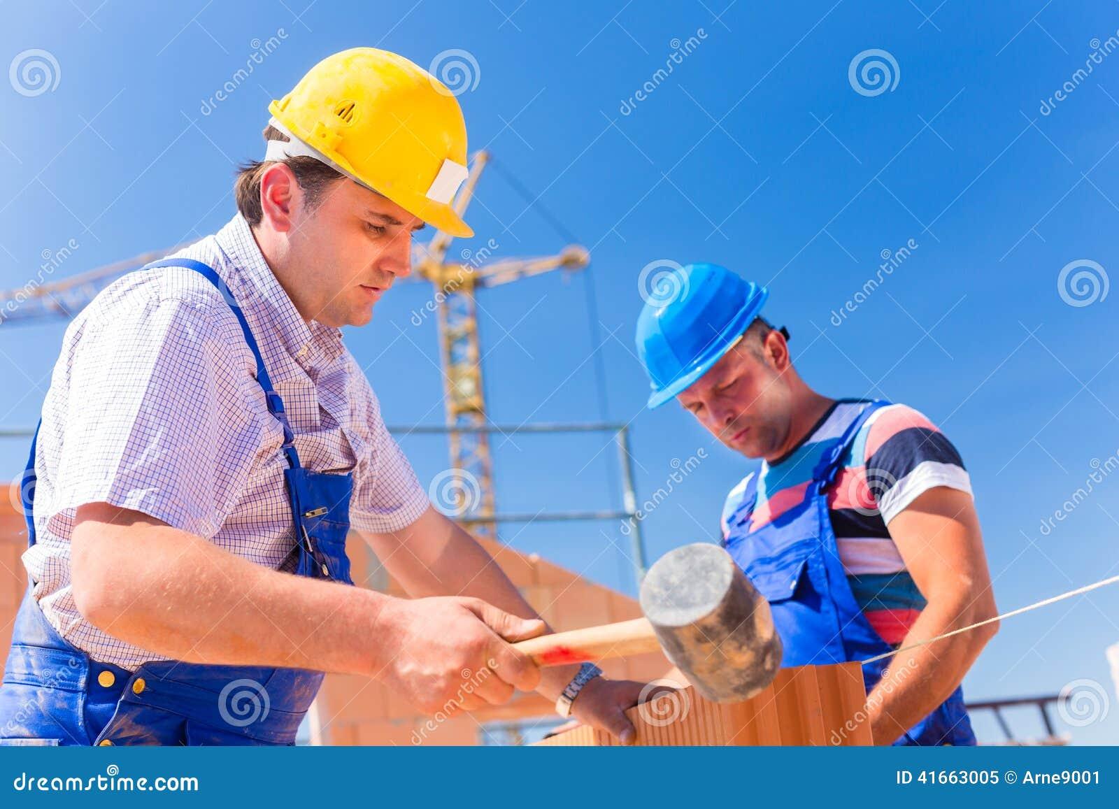 Работники строительной площадки строя стены на доме