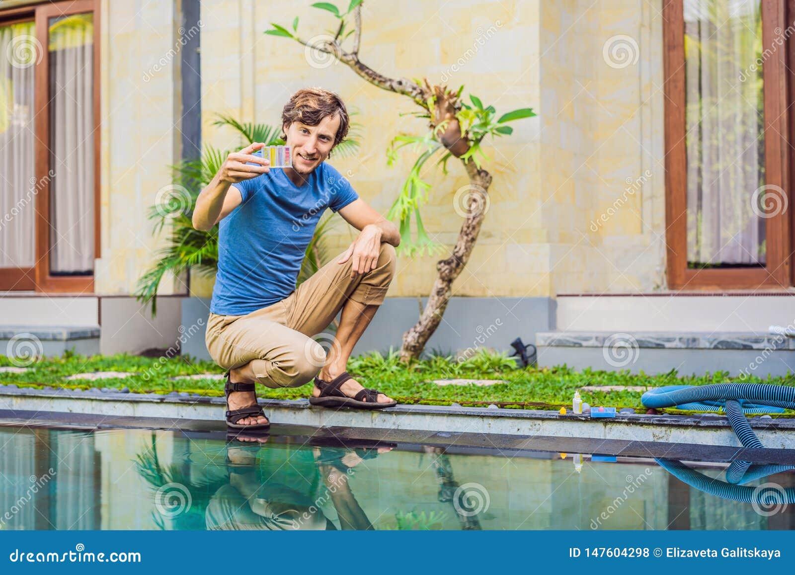 Работник бассейна проверяет бассейн для безопасности Измерение хлора и ПЭ-АШ бассейна