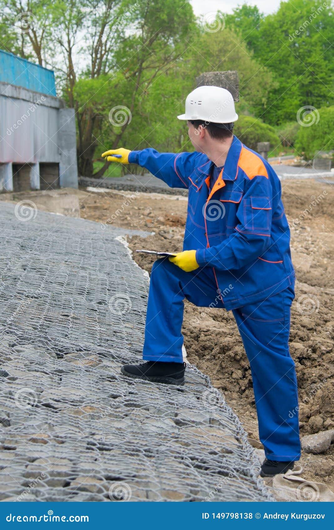 Работник в голубой форме, записывает конструкцию нового ландшафта и показывает объем работ