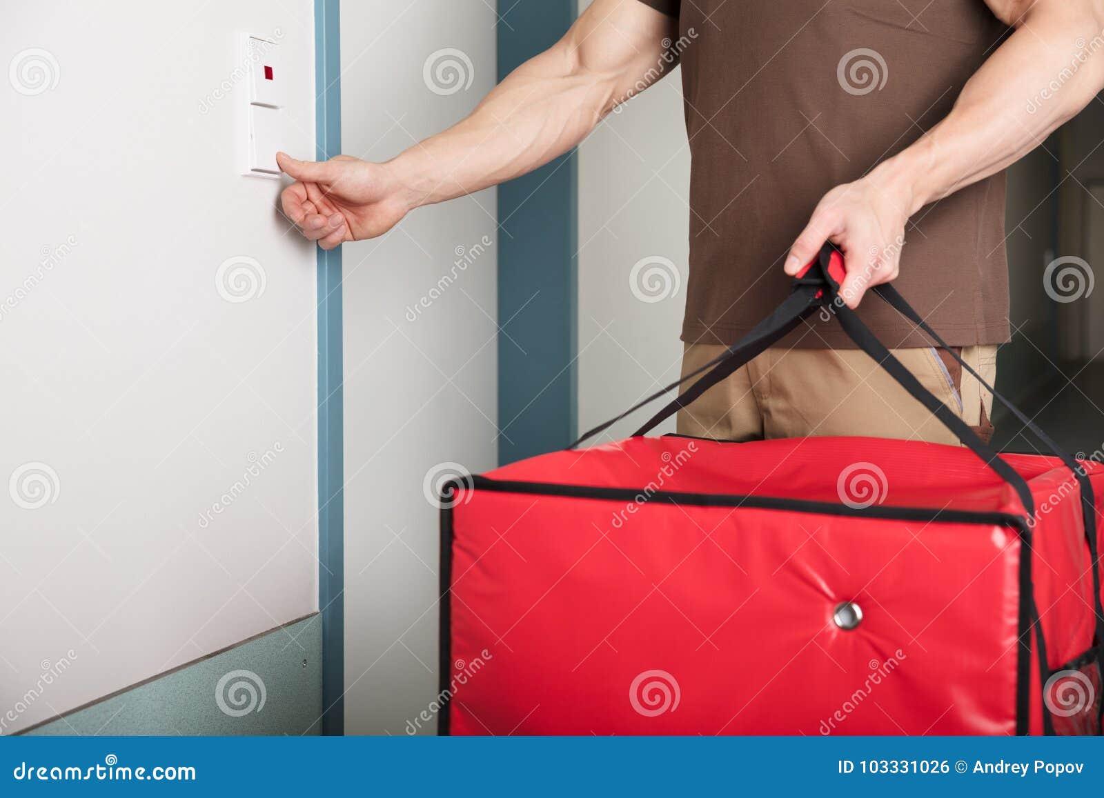 Работник доставляющий покупки на дом пиццы звеня дверной звонок