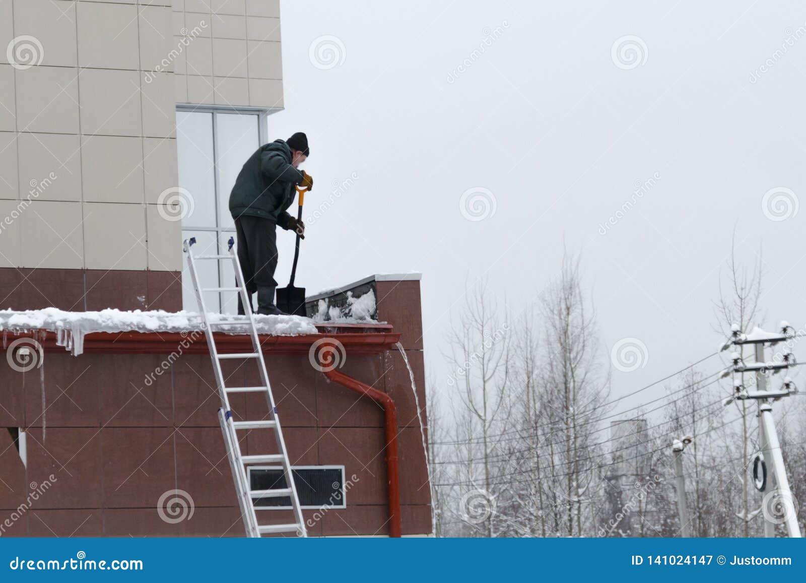 Работник извлекает снег и лед из крыши очищая крышу не исполняя с трудовыми правилами защиты
