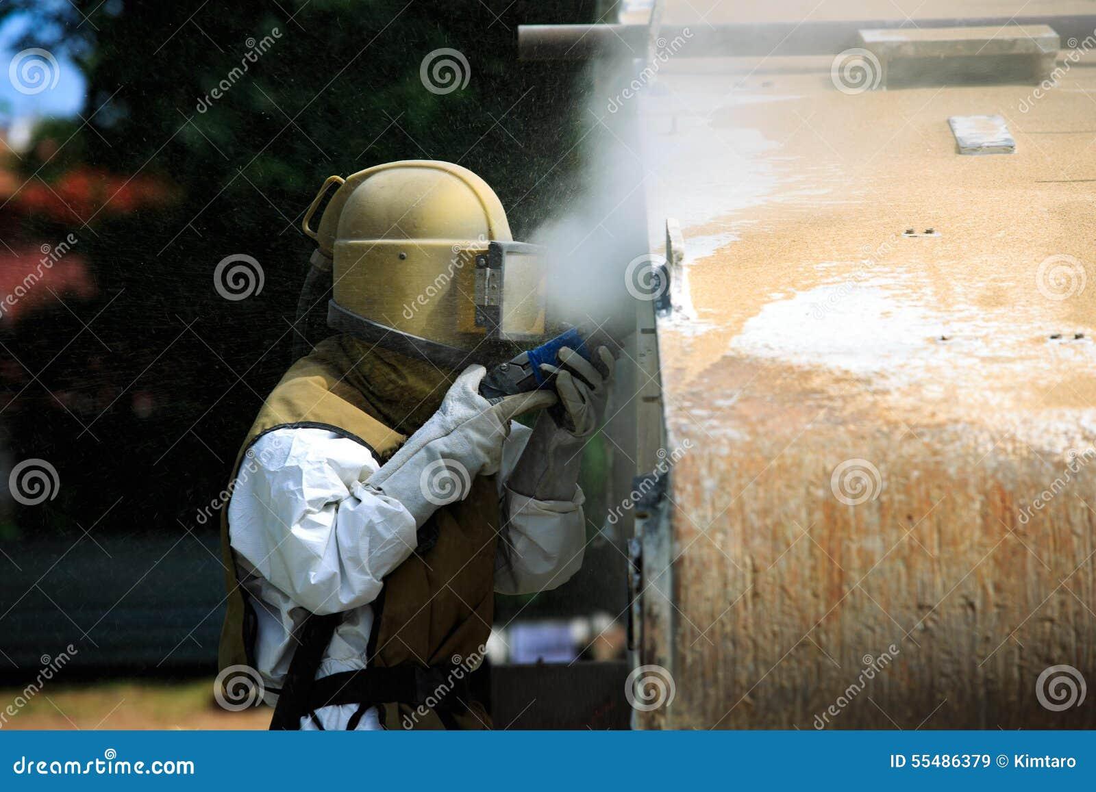 Работник извлекает краску взрывать песка воздушного давления
