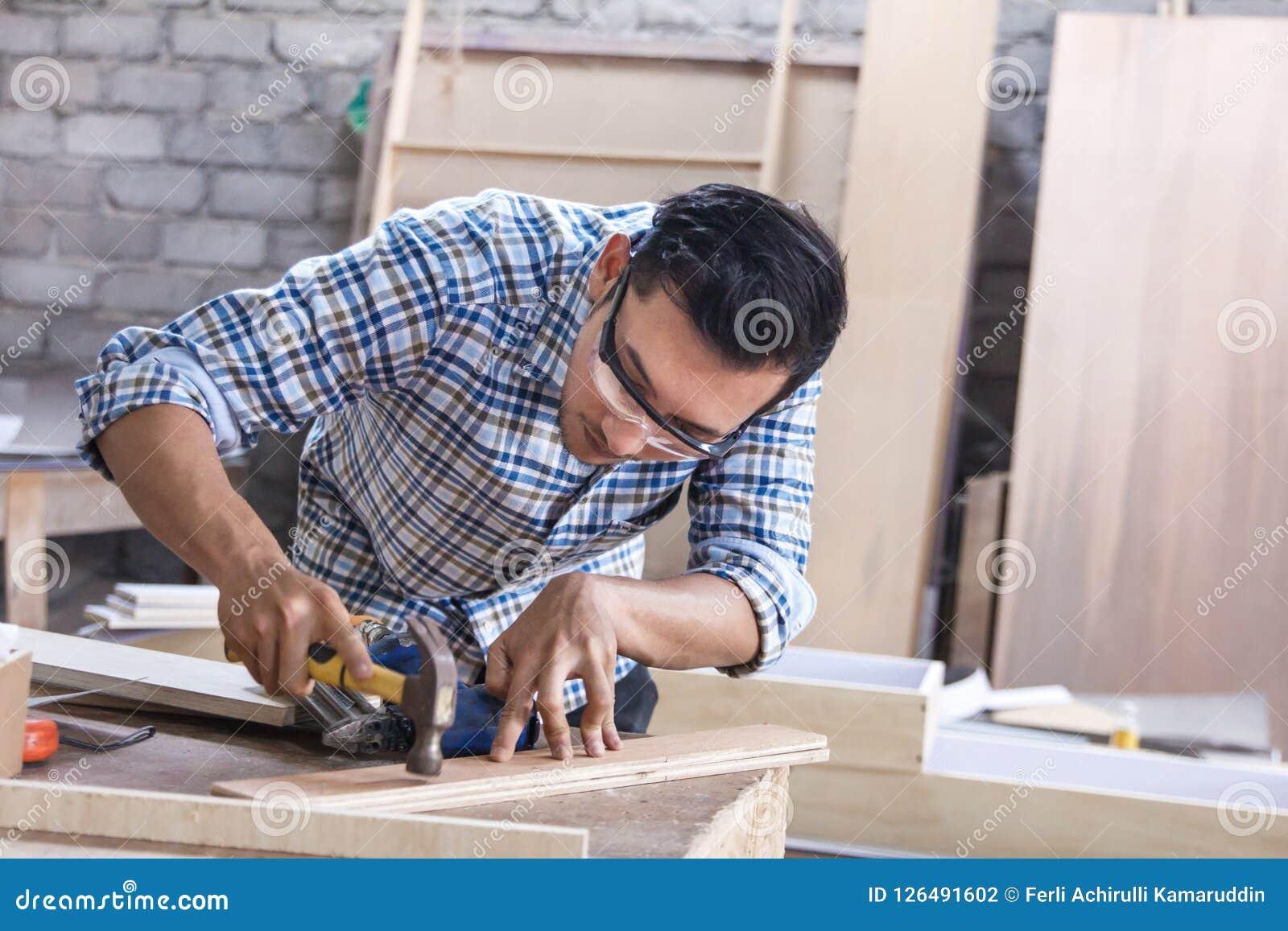 Работник на месте для работы плотника устанавливая ноготь используя молоток