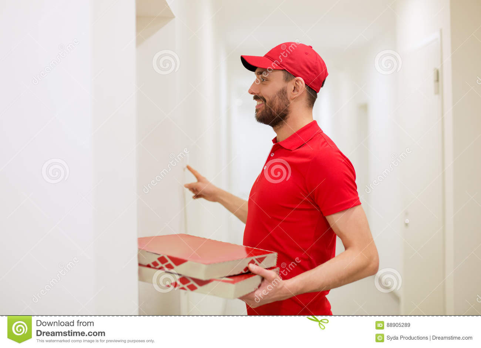 Работник доставляющий покупки на дом при коробки пиццы звеня дверной звонок