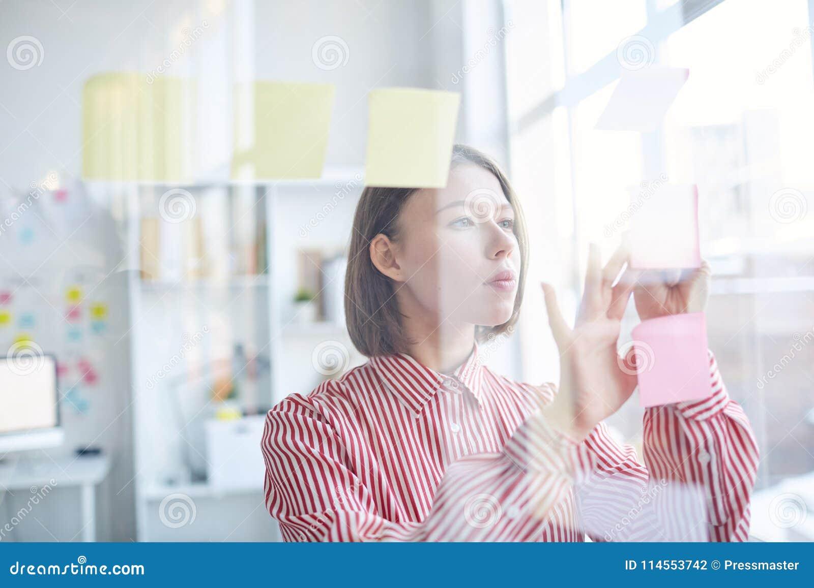Работник офиса читая липкие примечания