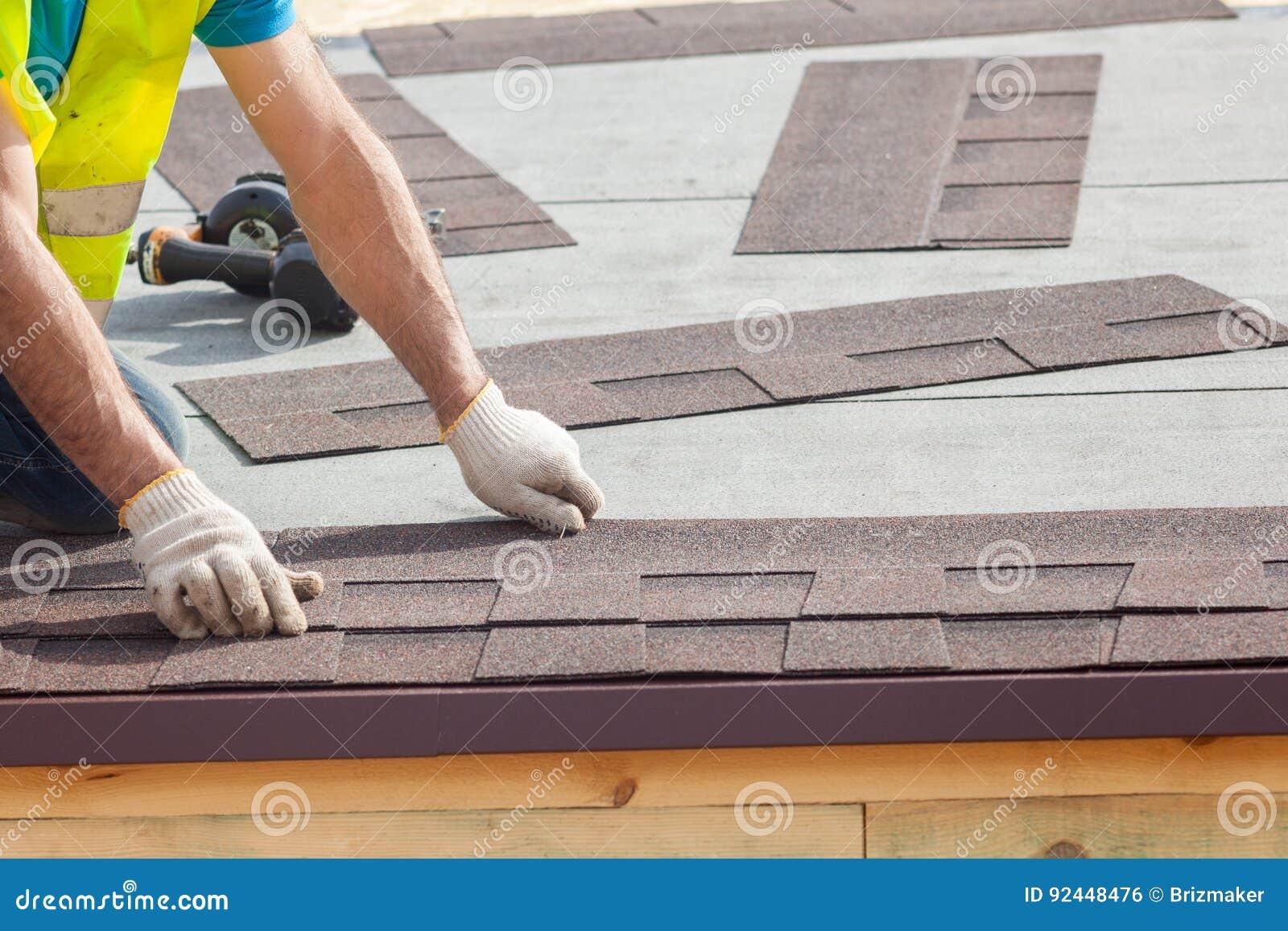 Работник построителя Roofer устанавливая гонт асфальта или плитки битума на новый дом под конструкцией