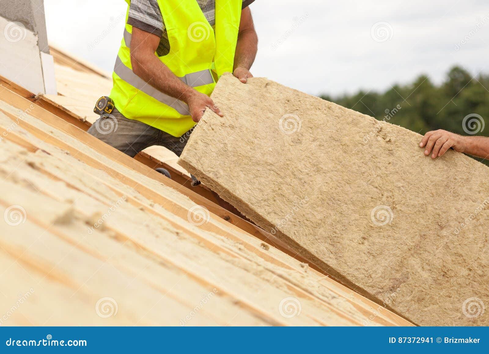 Работник построителя Roofer устанавливая материал изоляции крыши на новый дом под конструкцией
