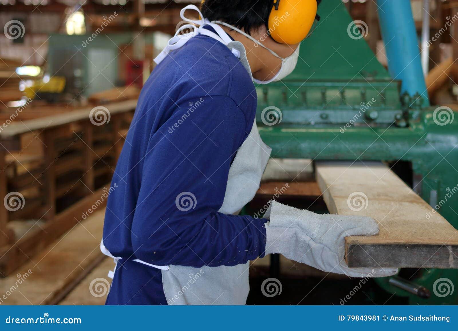 Работник работает с строгать деревянной машины Он носит оборудование для обеспечения безопасности в фабрике изолированная белизна