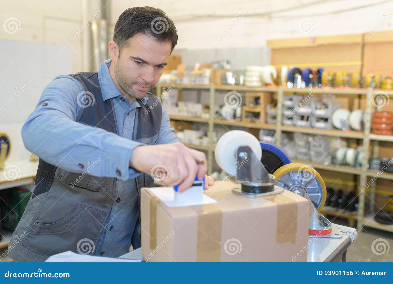 Работник склада подготавливая пересылку в большой склад
