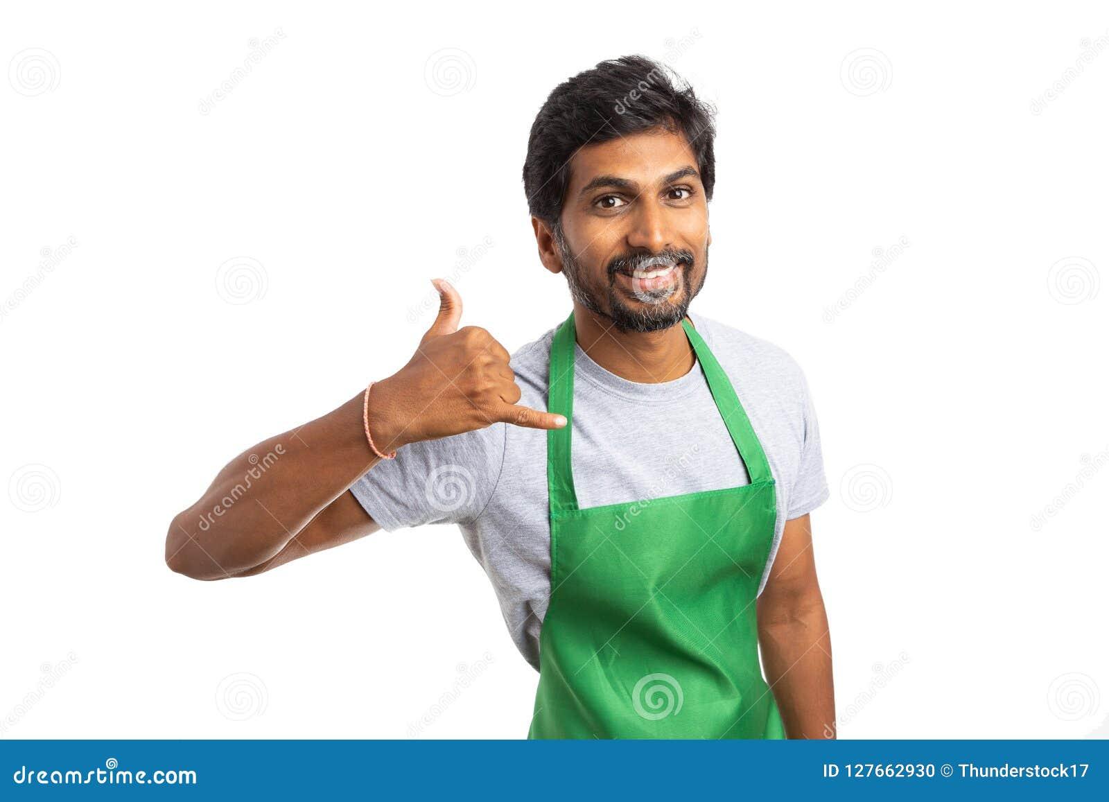 Работник супермаркета держа жест мобильного телефона на ухе