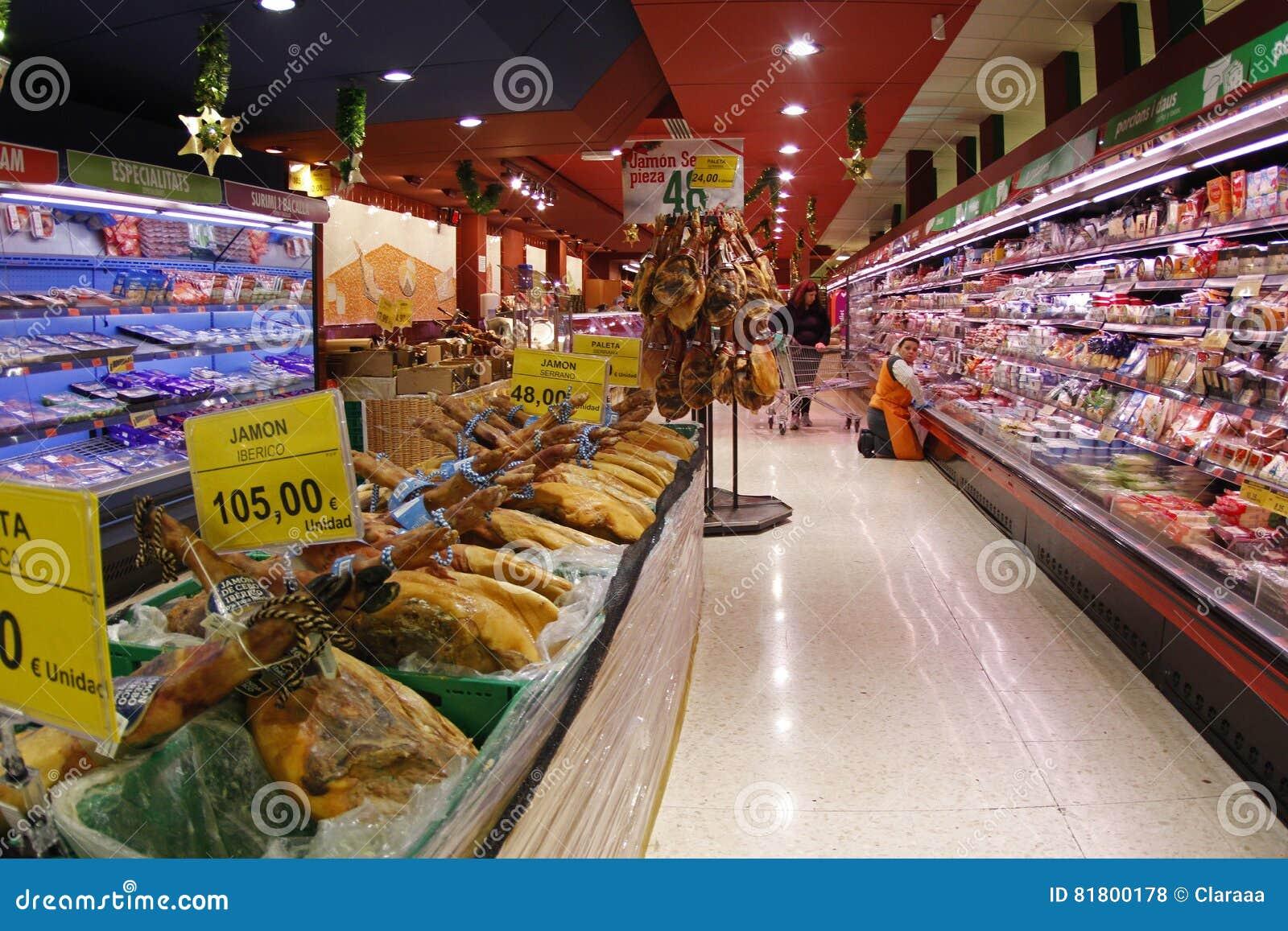 Работник супермаркета пополняя запас в холодильниках