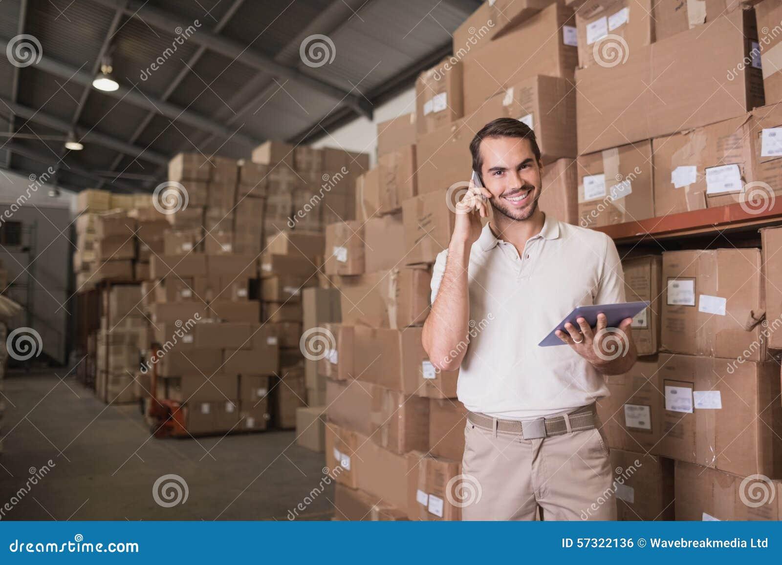 Работник с мобильным телефоном и цифровой таблеткой в складе
