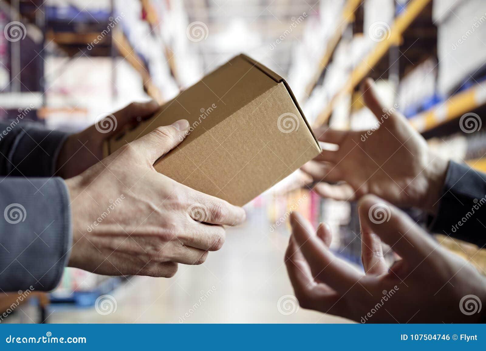 Работник с пакетом в складе распределения