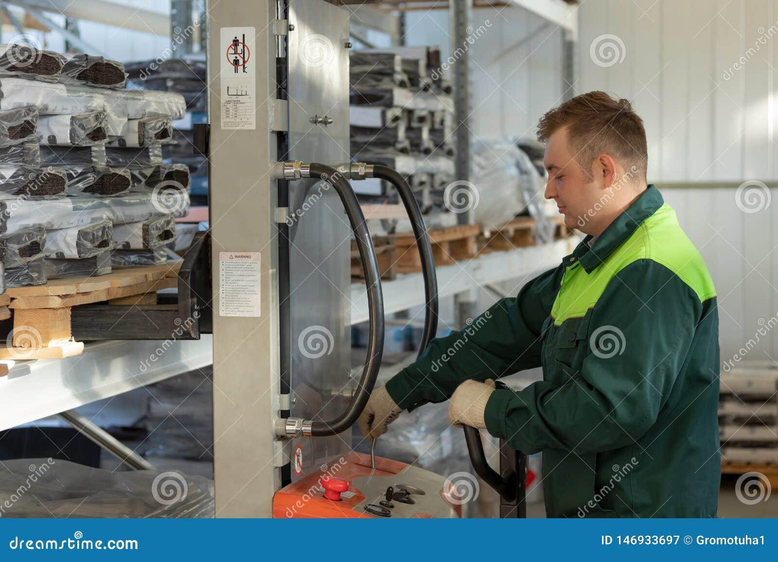 Работник управляет грузоподъемником в складе