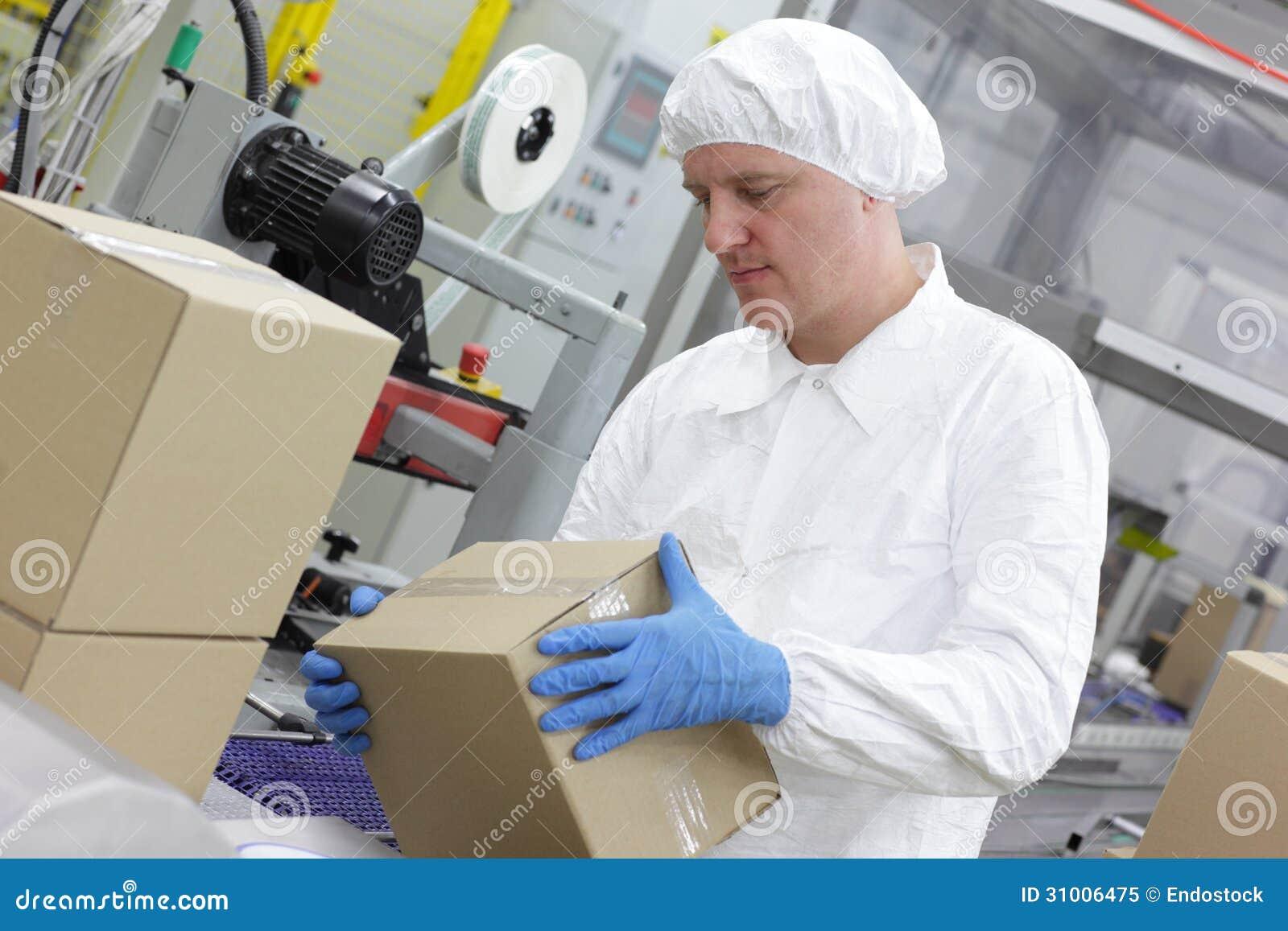 Работник физического труда на производственной линии общаясь с коробками