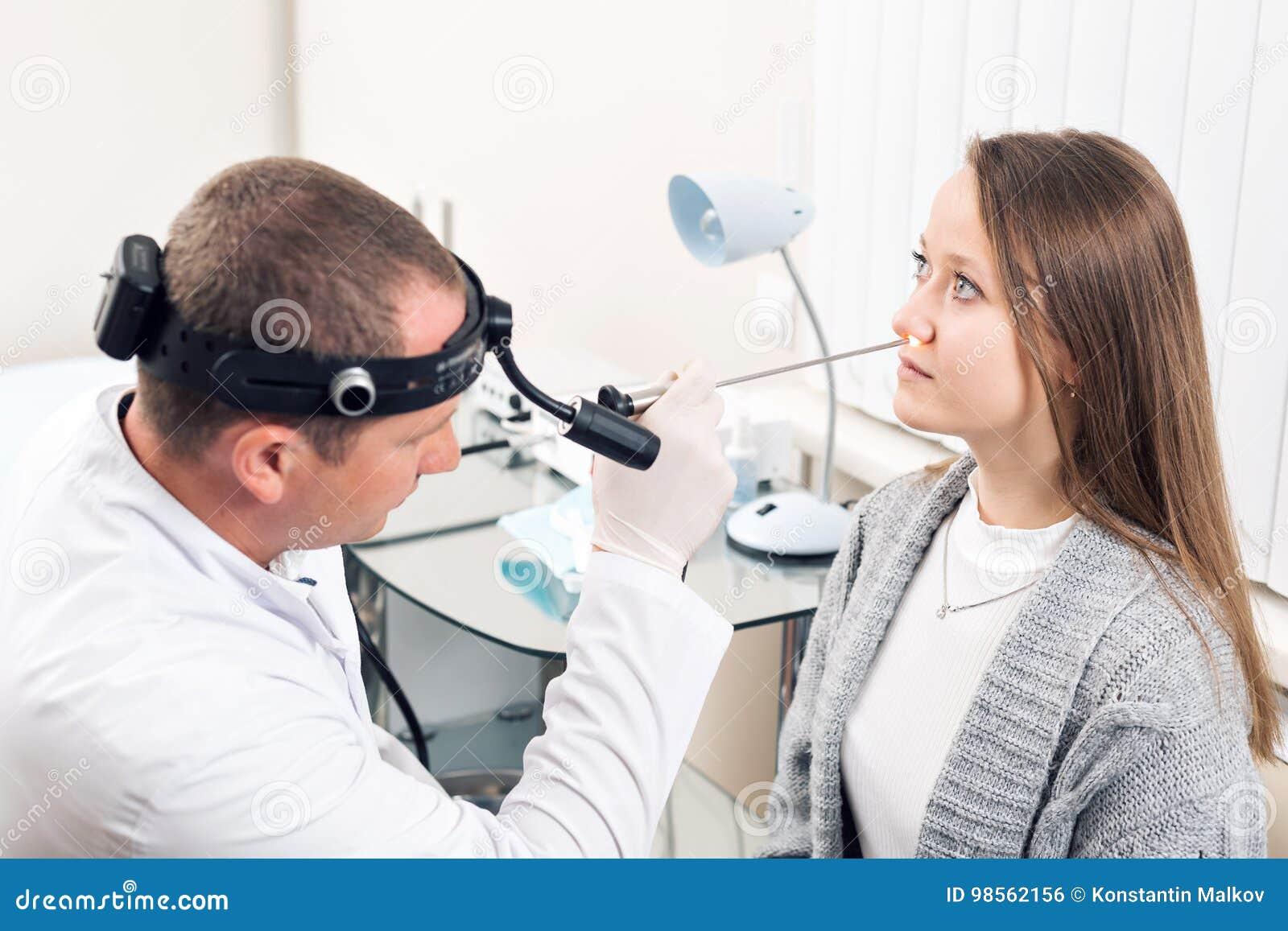 Работник Otolaryngologist очень внимательный медицинский смотря нос его посетителя