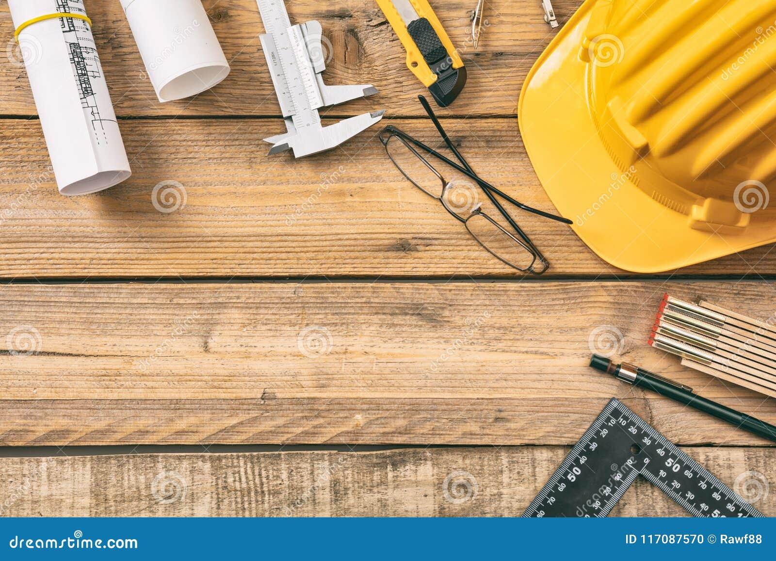 Рабочее место архитектора Запроектируйте светокопии конструкции и инструменты инженерства на деревянном столе, копируют космос