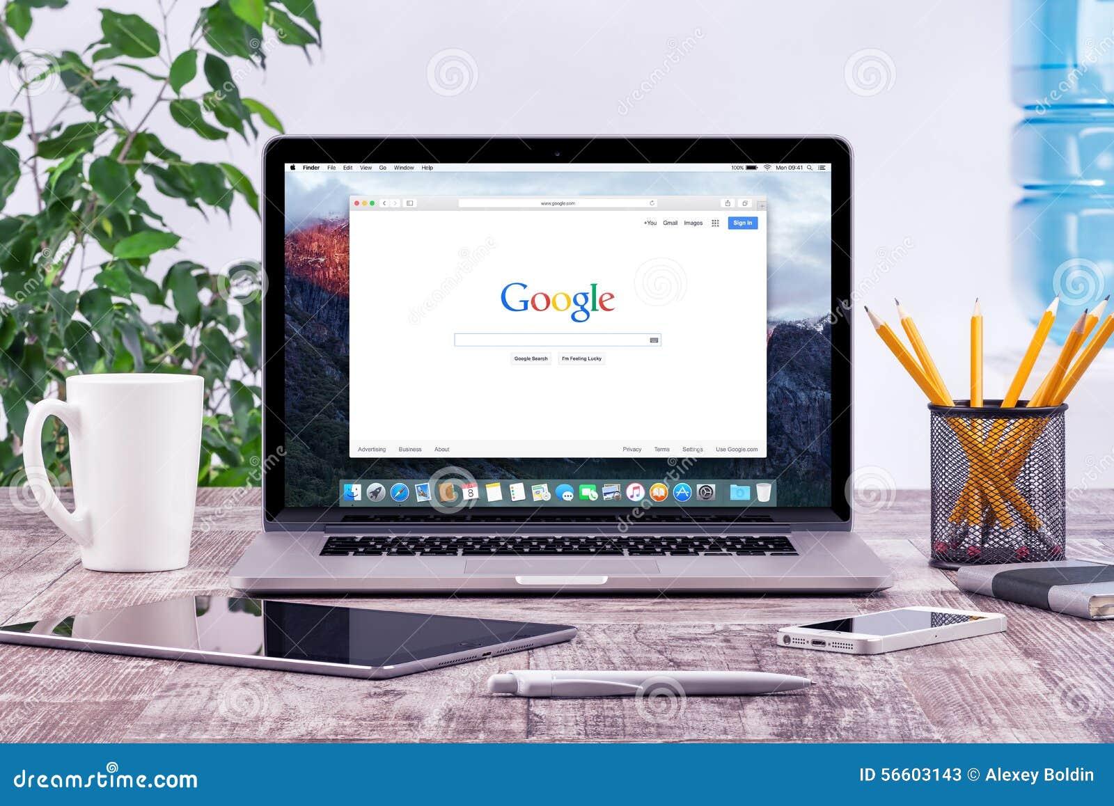 Рабочее место офиса с открытым Яблоком Macbook Pro с страницей Google