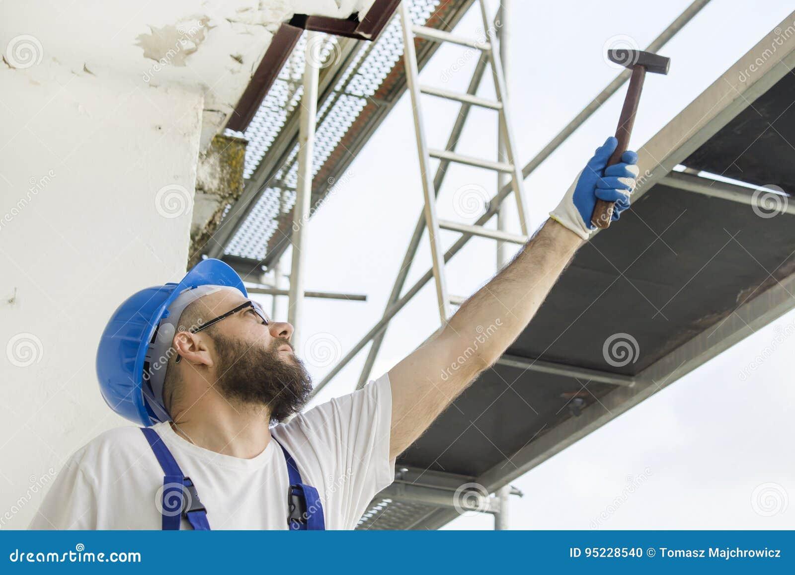 Рабочий-строитель в одежде работы, защитных перчатках и шлеме на голове дает молоток Работа на большой возвышенности ремонтина