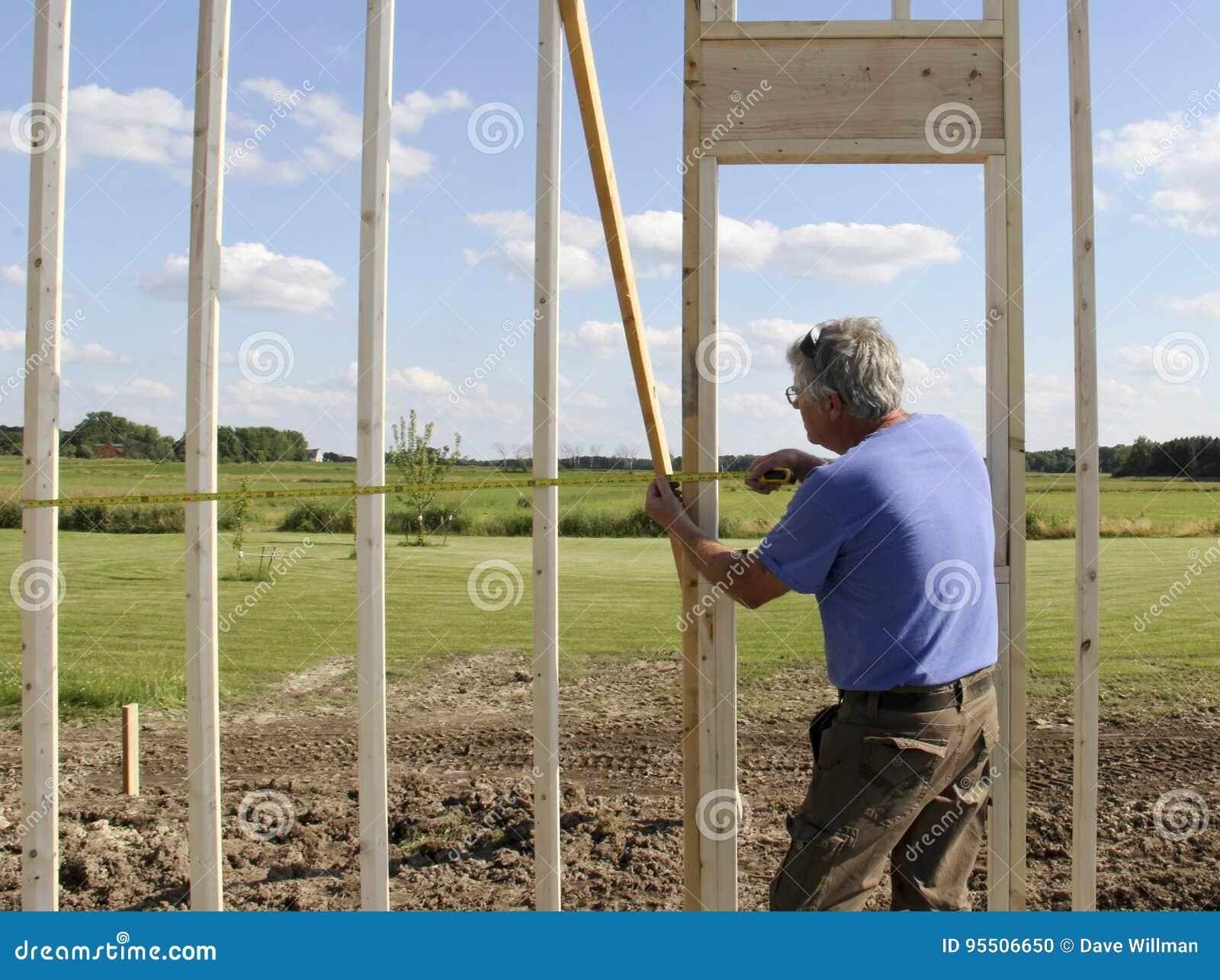 Рабочий-строитель используя правителя