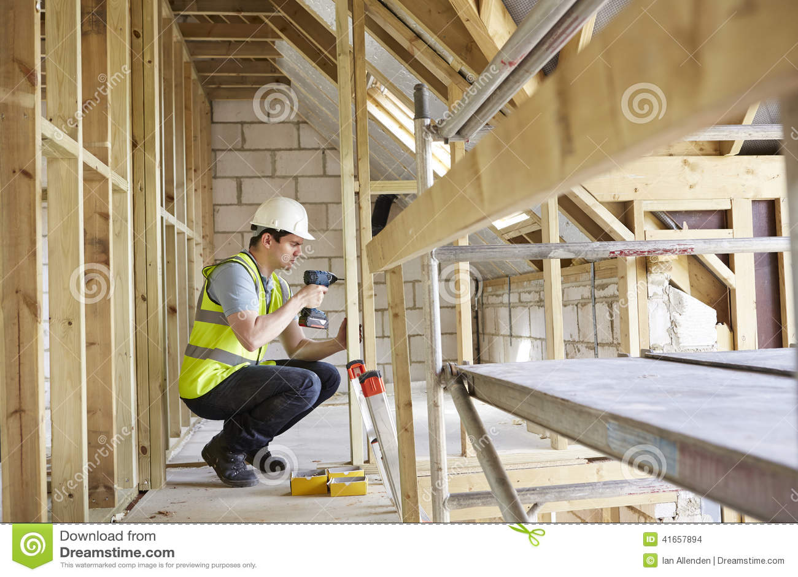 Рабочий-строитель используя сверло на строении дома