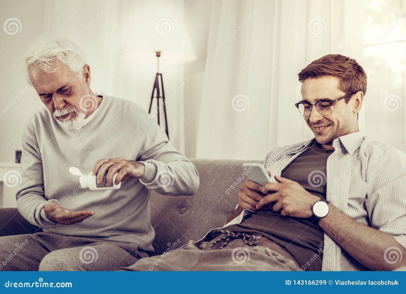 Равнодушный внук смотря телефон между тем его дедушка принимая таблетки