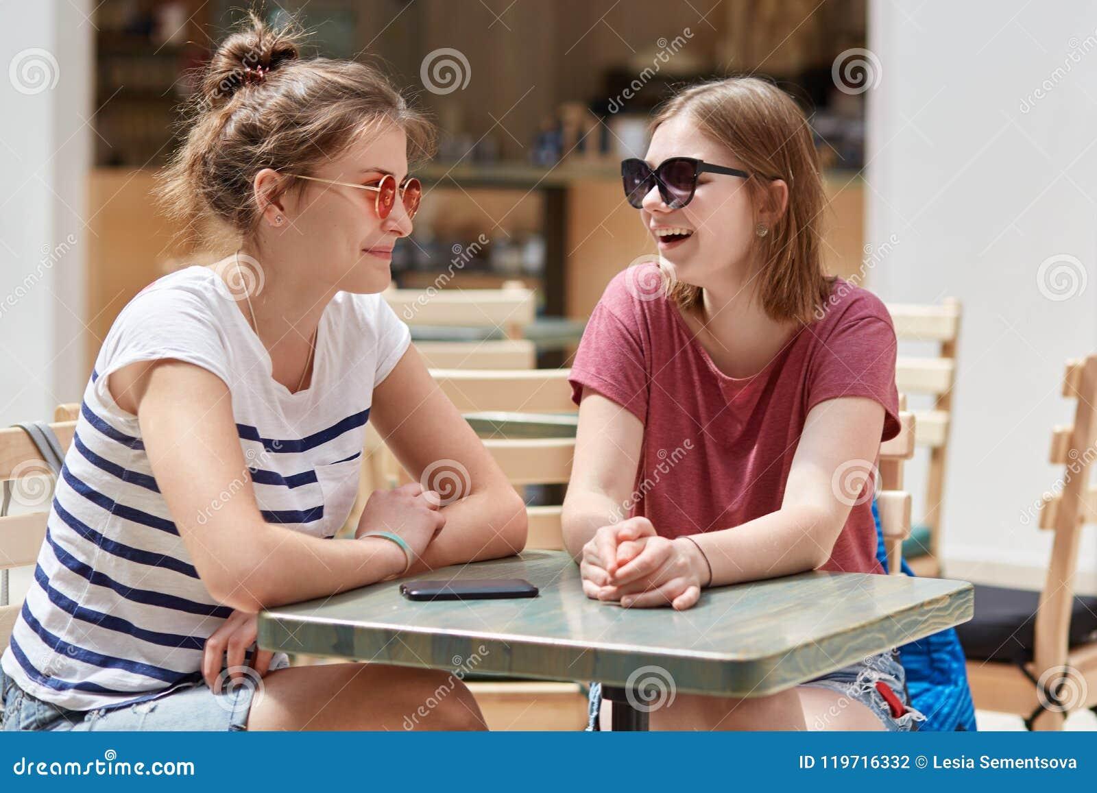 Радостные женские товарищи в тенях, имеют дружелюбную беседу в кофейне пока ожидание для заказа, имеет потеху совместно, recreat