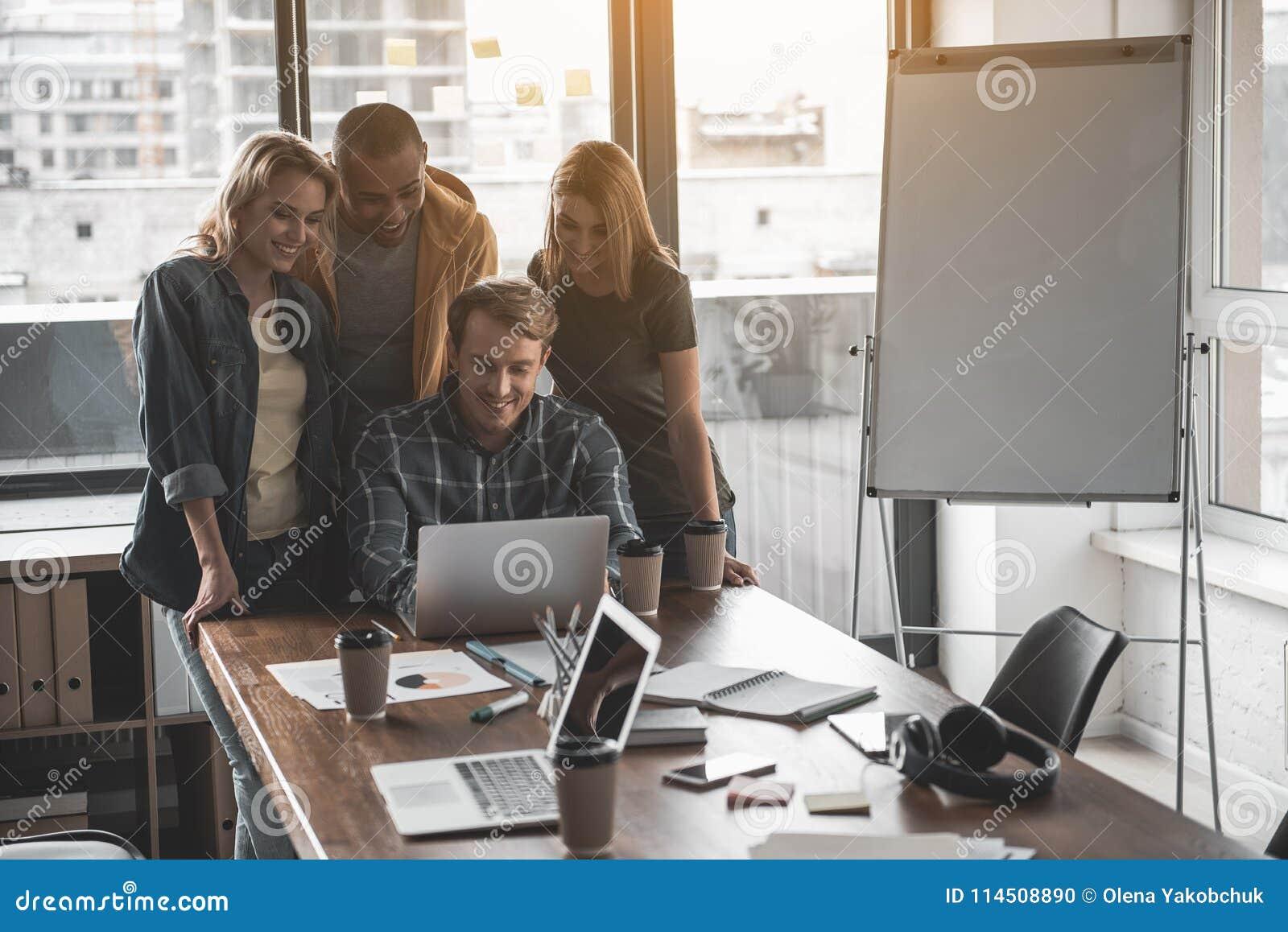 Радостные сотрудники вытаращить на экране компьютера