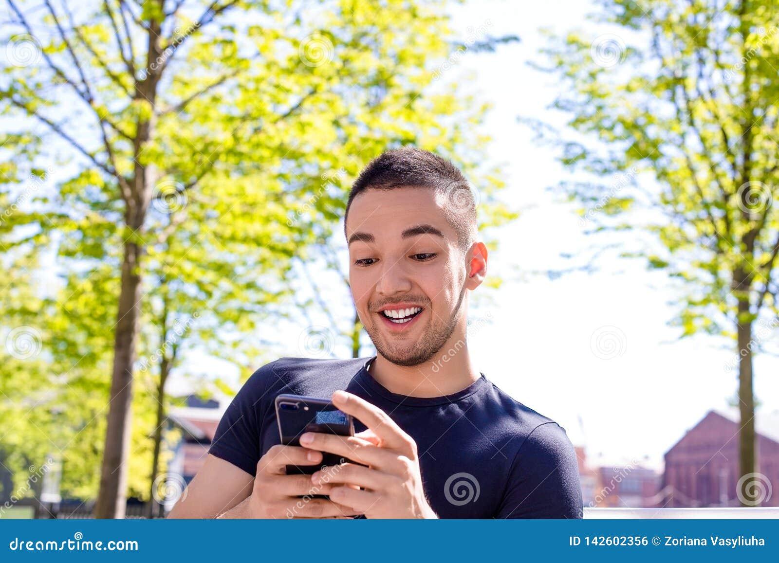 Радостный подросток играя игры на смартфоне во время остатков outdoors