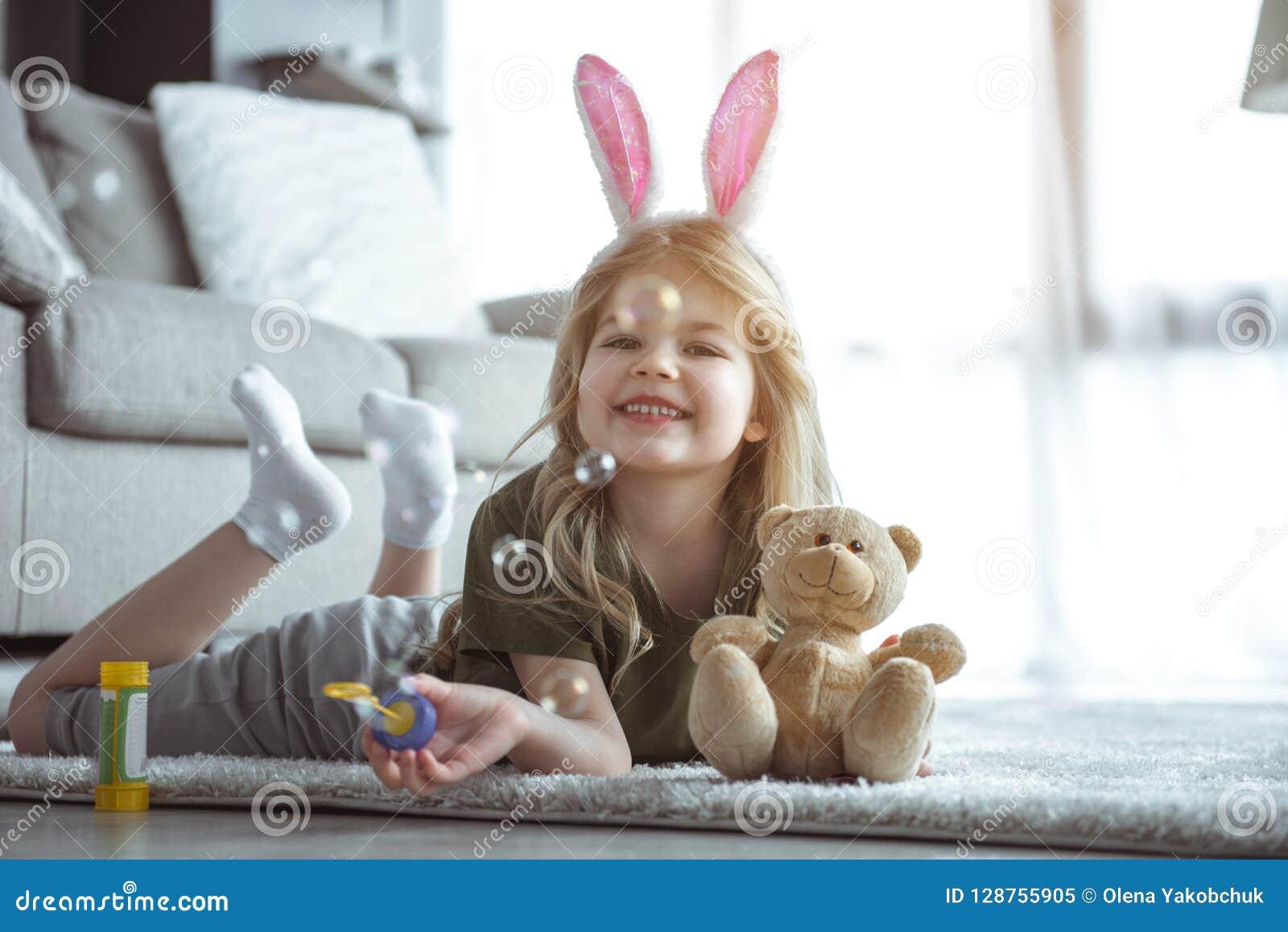 Радостный ребенок имея потеху с игрушками дома
