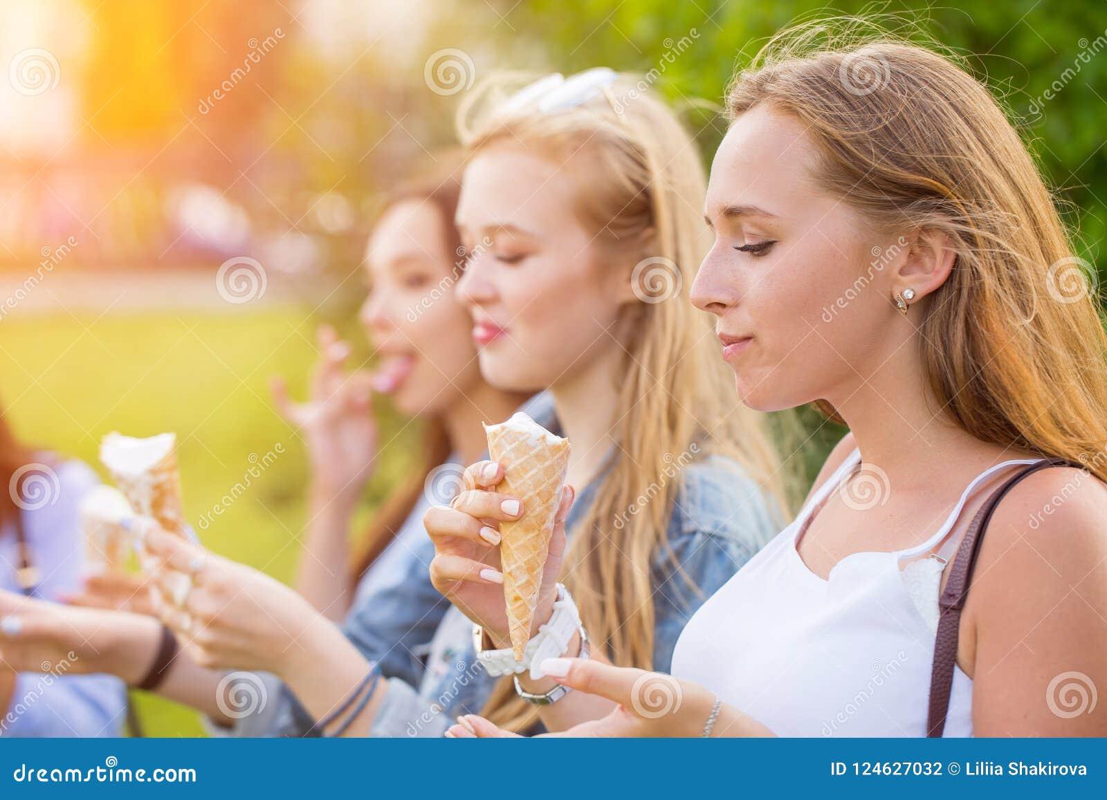 3 радостных молодых подруги на прогулке стоя в ряд усмехающся счастливо едят конусы мороженого на летних каникулах
