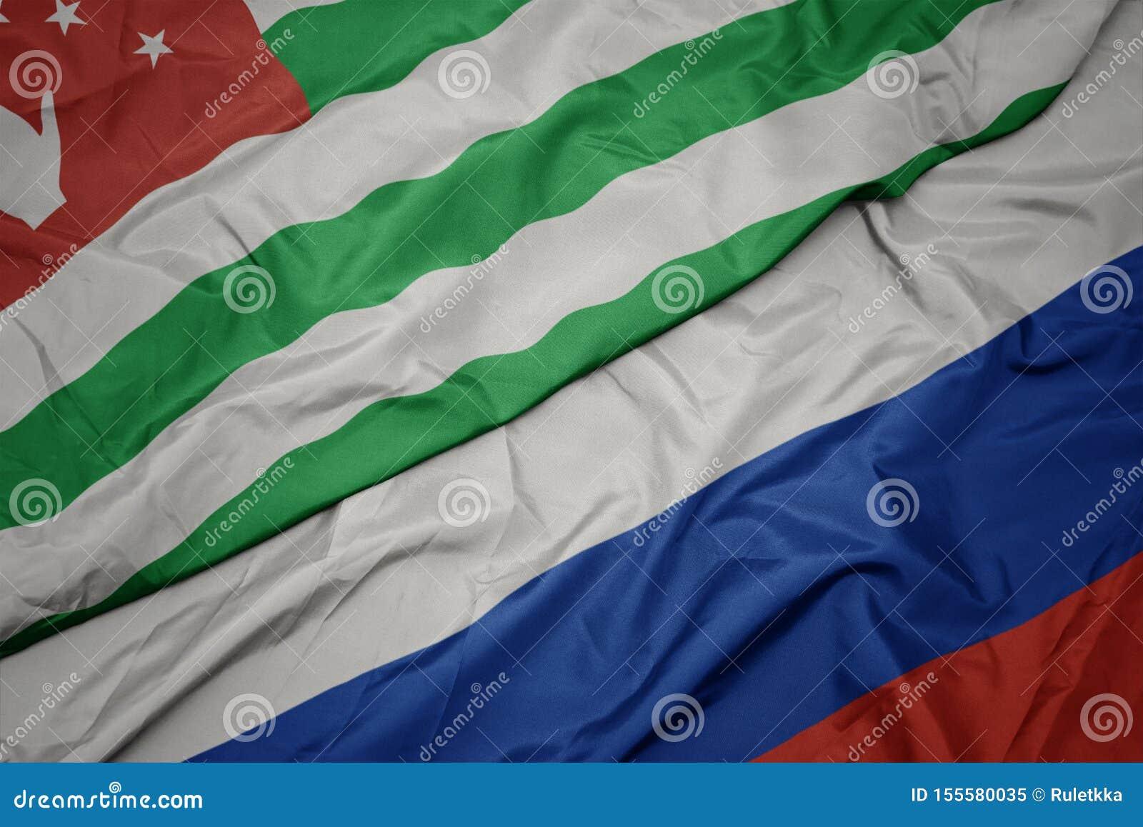 развевая красочный флаг России и национальный флаг абхазии