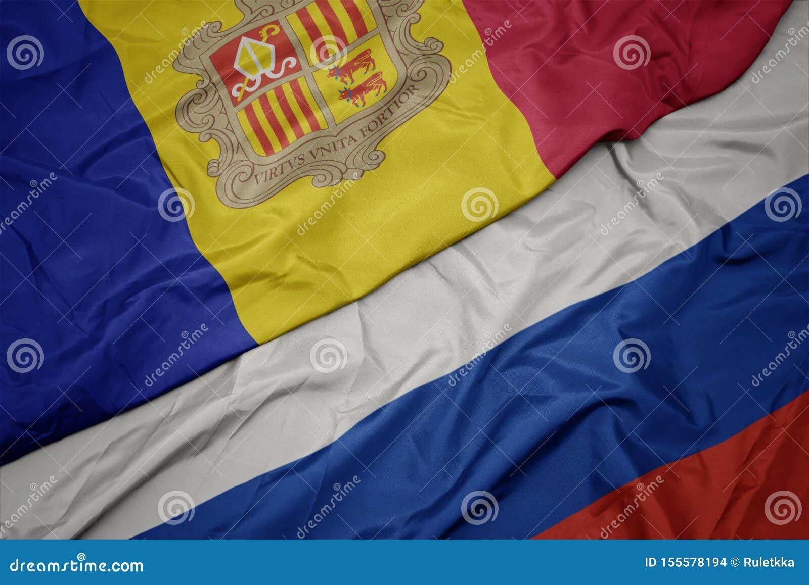 развевая красочный флаг России и национальный флаг Андорры