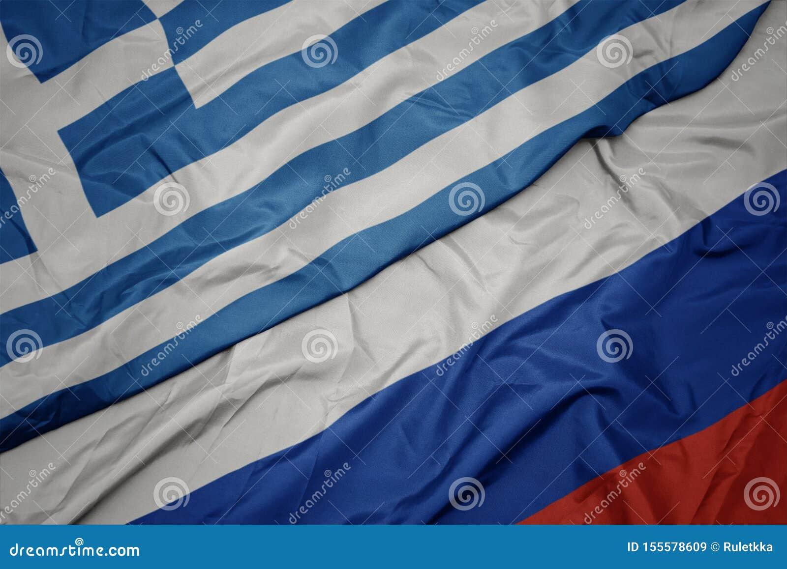 развевая красочный флаг России и национальный флаг Греции