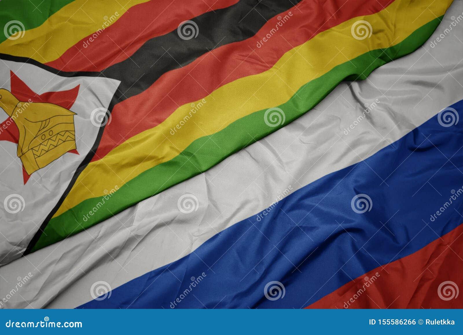развевая красочный флаг России и национальный флаг Зимбабве