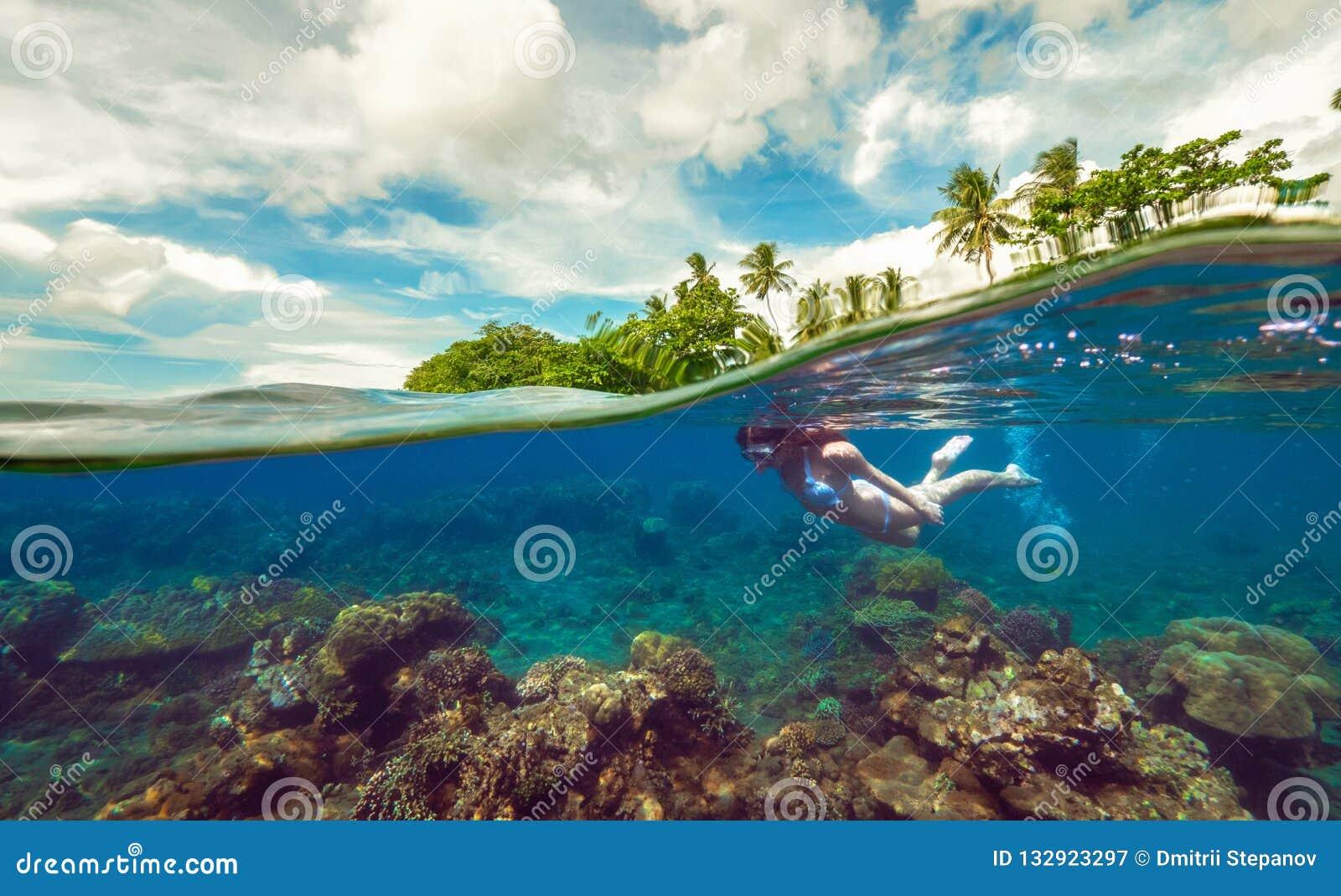 Разделенное подводное фото девушки с маской в тропическом океане наслаждаясь летними каникулами на экзотическом острове