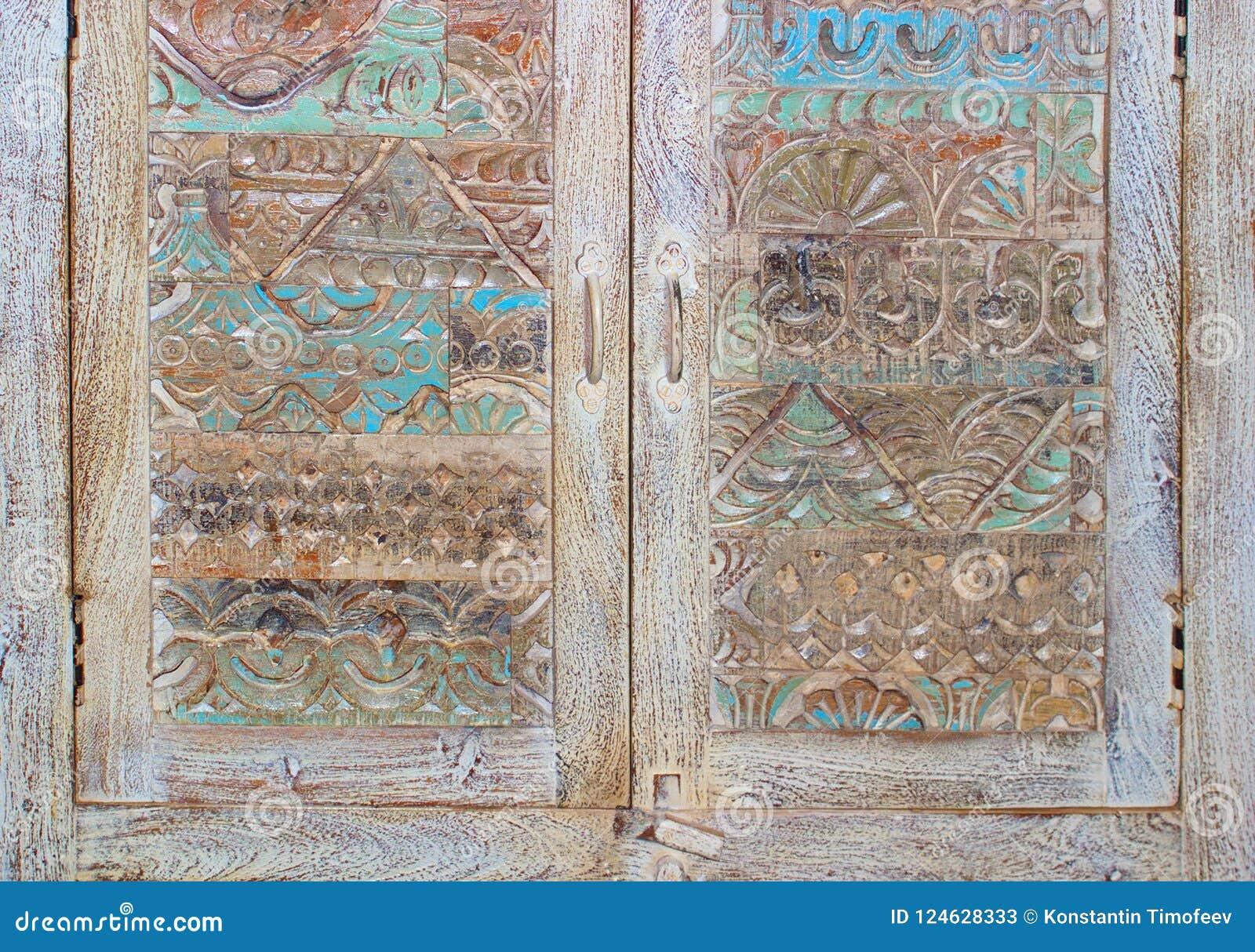Разделите винтажным двери высекаенные антиквариатом к востоку от комода