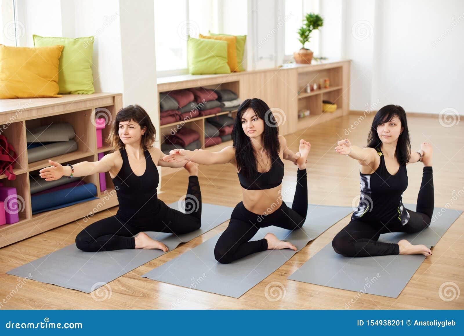 Раздумье группы людей делая сидя представление йоги в роскошный фитнес-центр Женщины практикуя asana вызвали представление голубя