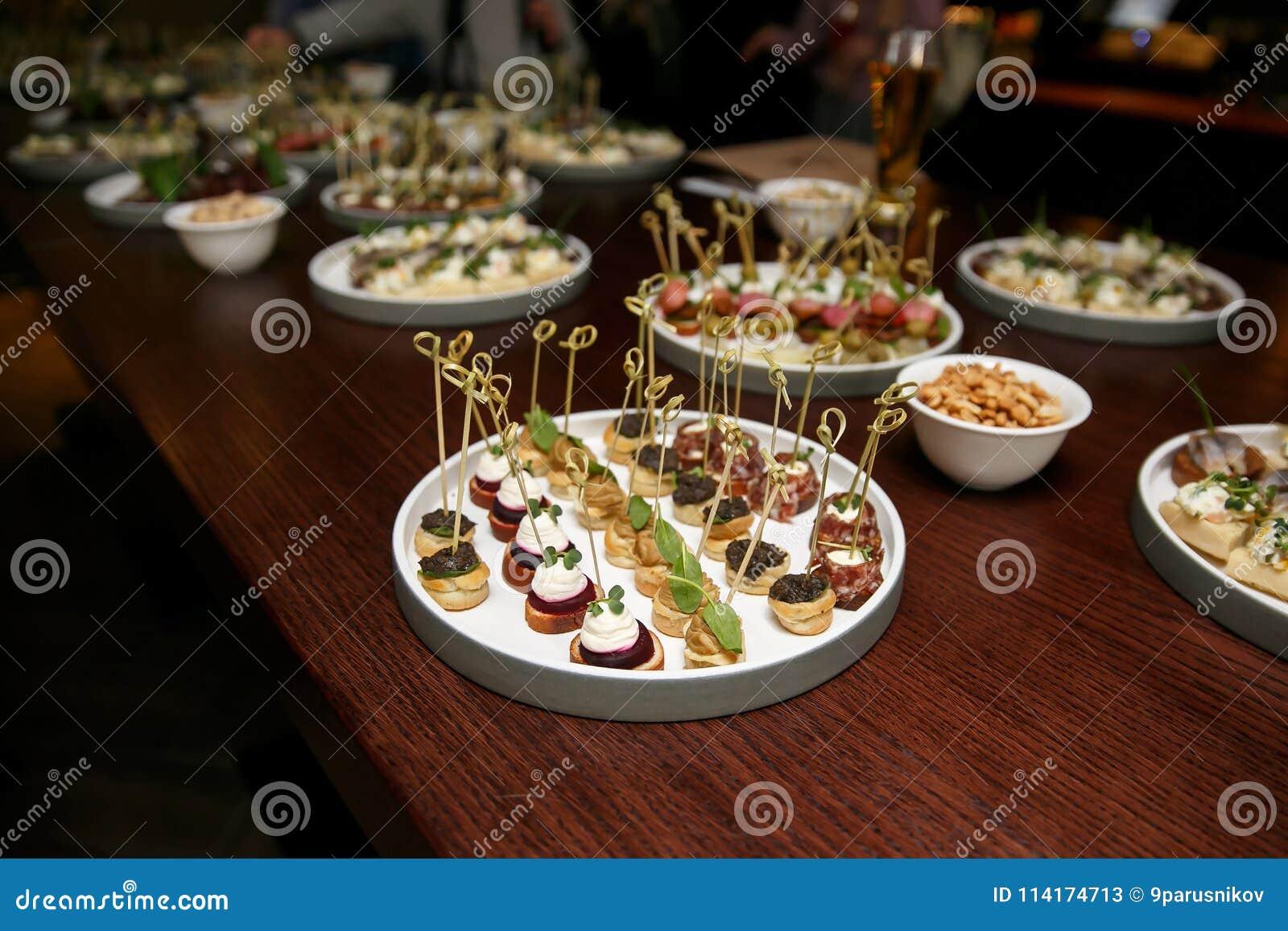 Различные закуски и закуски еды в круглых плитах на корпоративном событии party Торжество с таблицей банкета ресторанного обслужи