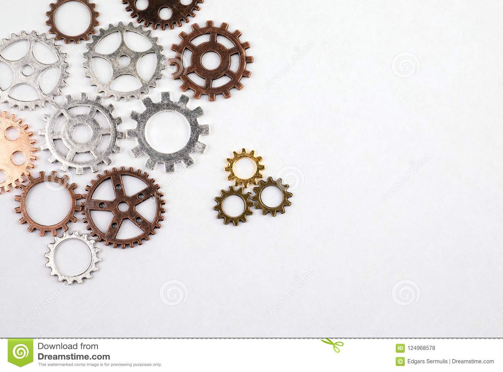 Различные размеры и покрашенные шестерни на белой предпосылке