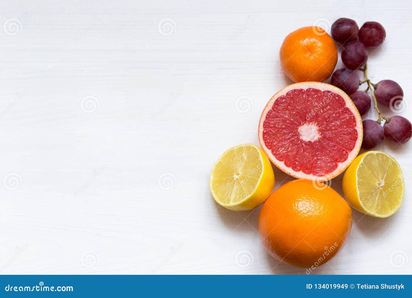 Различные цитрусовые фрукты на белой предпосылке, взгляде сверху, космосе экземпляра