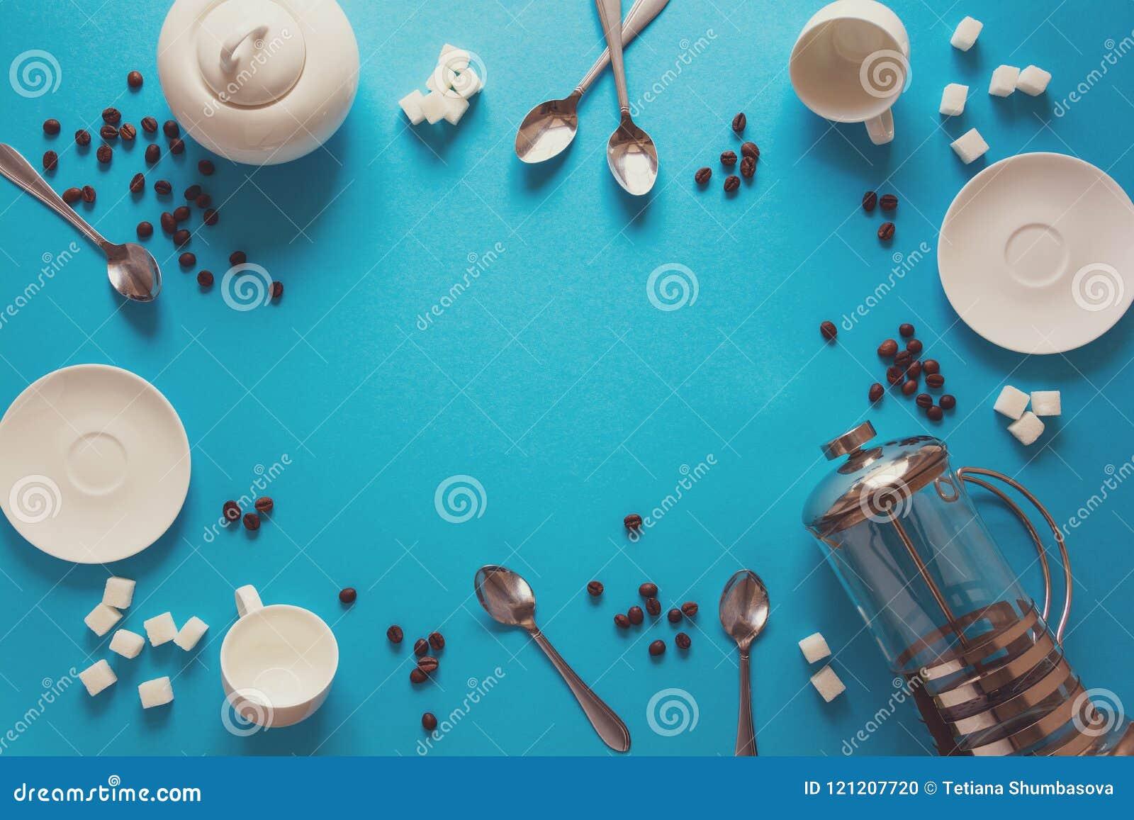 Различный кофе делая аксессуары: Французские пресса кофе, чашки, поддонники, кофейные зерна, ложки и сахар на предпосылке голубой