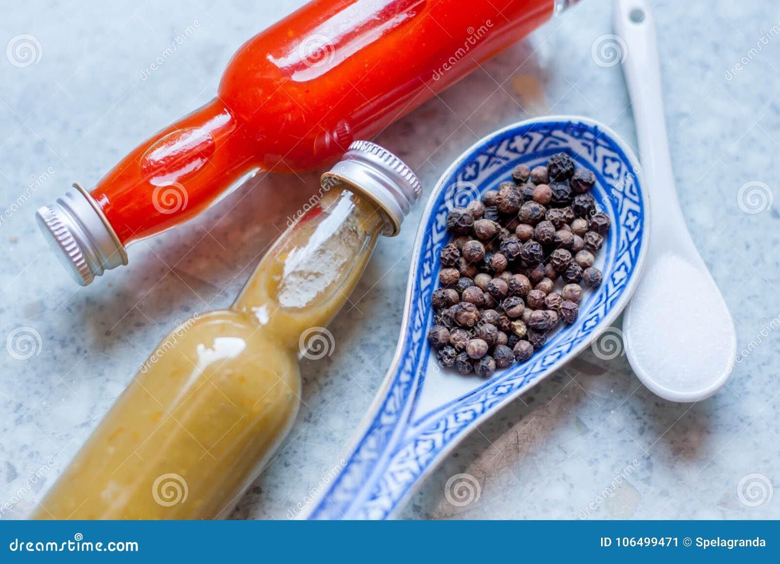 2 различных горячих соусы, соль и перца