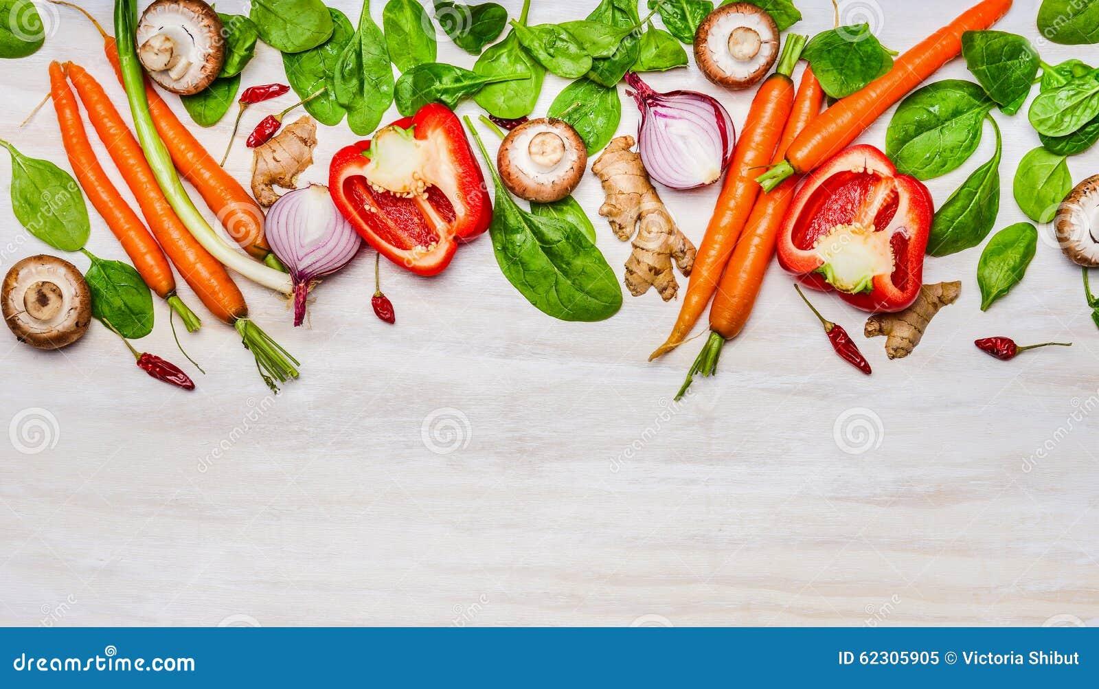 Разнообразие ингридиентов овощей для здоровой еды и варить на белой деревянной предпосылке, взгляд сверху