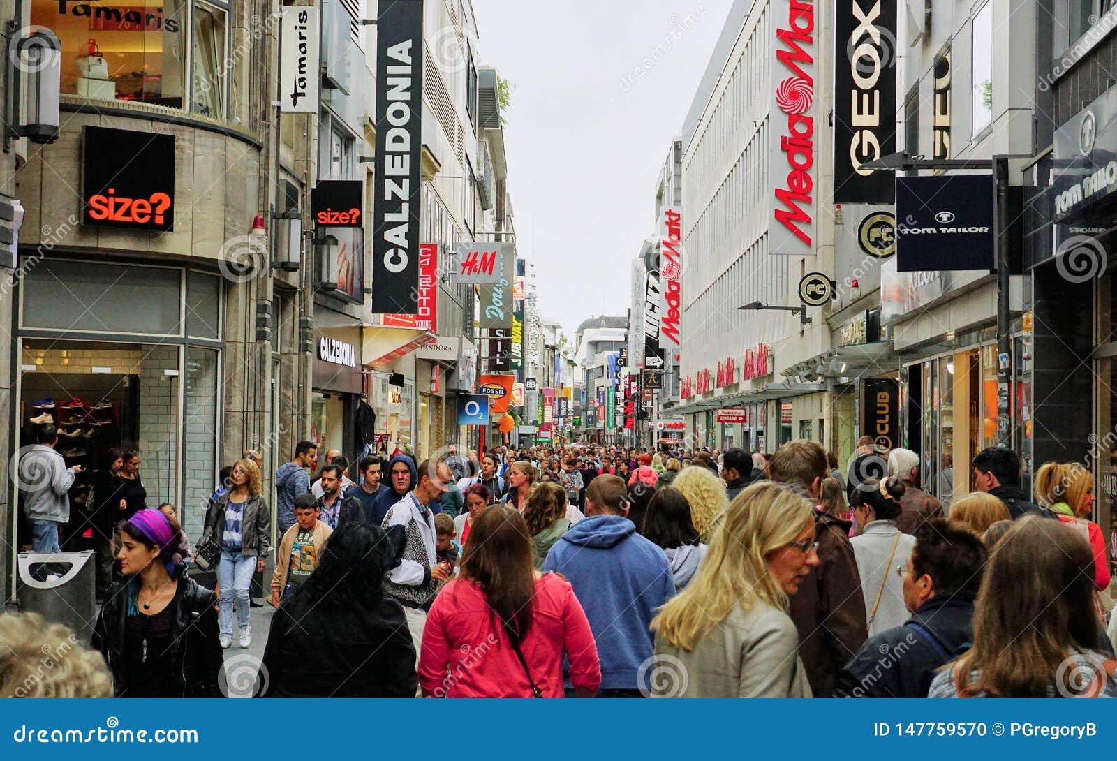 Разнообразная толпа заполняет главную улицу торгового района в Кёльне, Германии