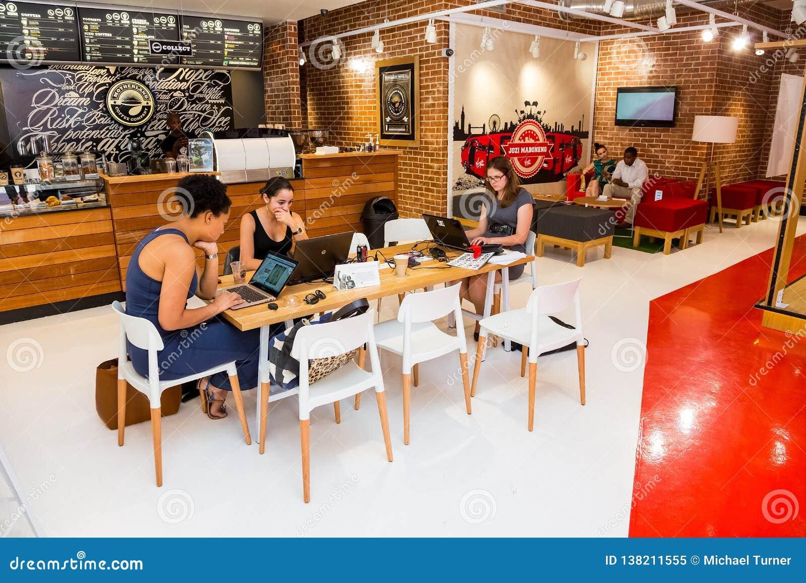 Разнообразные женские клиенты используя интернет в кофейне