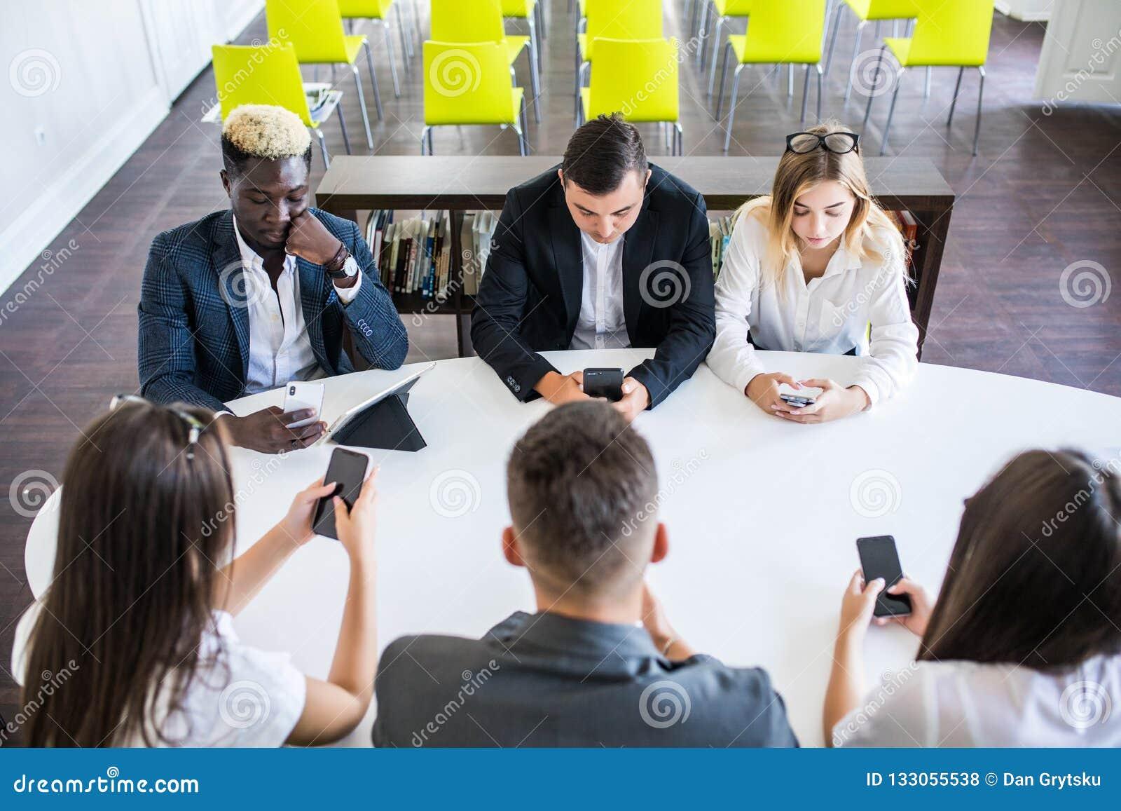 Разнообразные люди офиса работая на мобильных телефонах Корпоративные работники держа смартфоны на встрече Серьезное multiracial