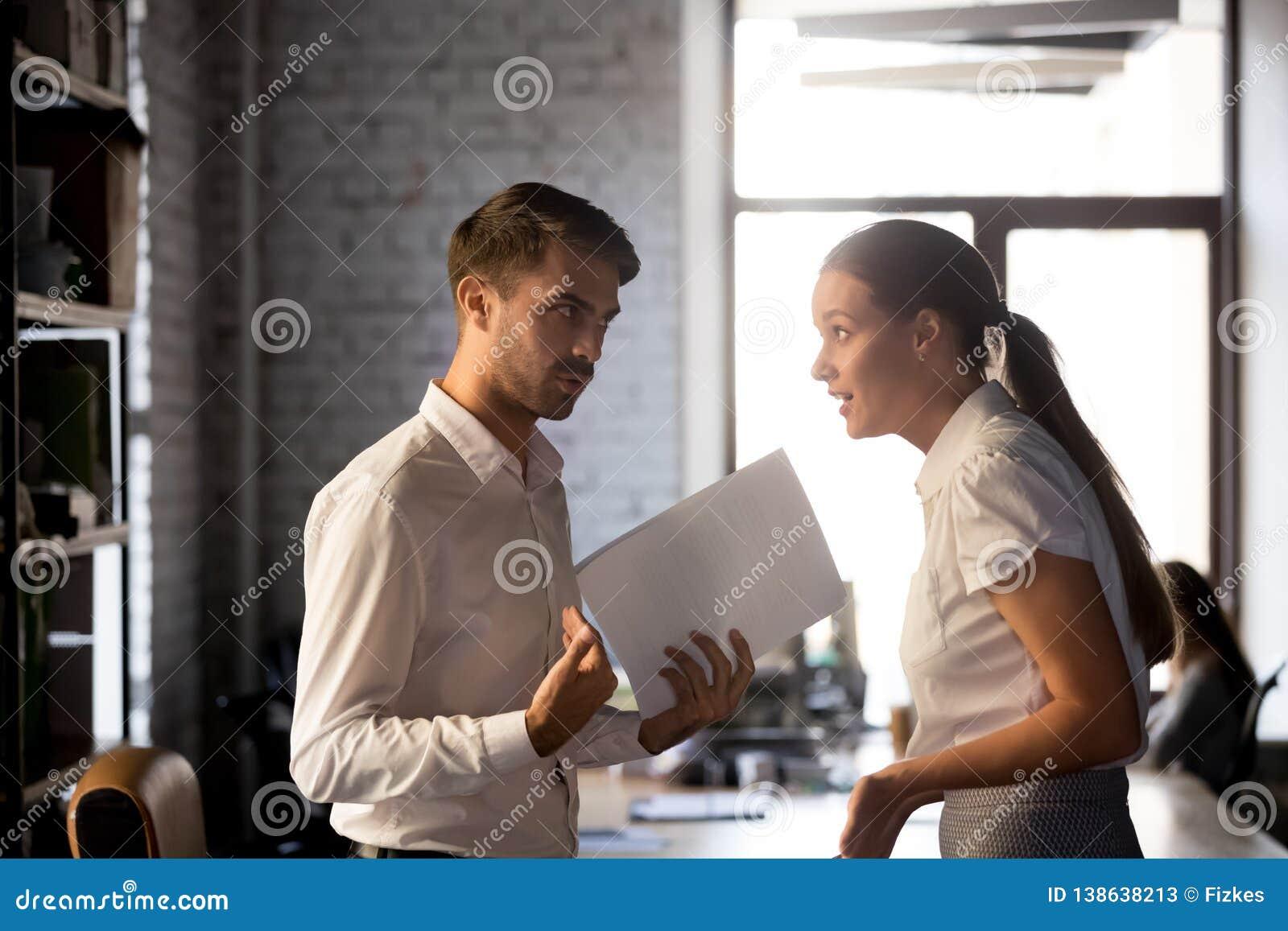 Разнообразные работники спорят над финансовым отчетом в офисе