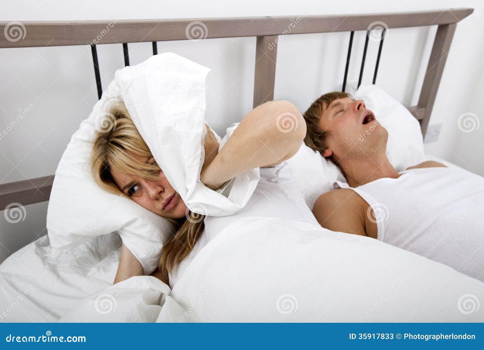 Разочарованные уши заволакивания женщины с подушкой пока человек храпя в кровати